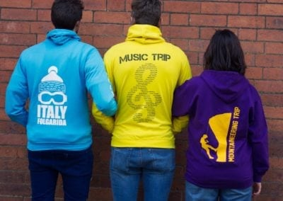 2 men and a woman, backs to the camera, wearing three different styles of hoody